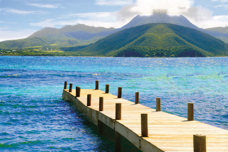 A wooden dock sits with calm blue water and a view of lush mountains.