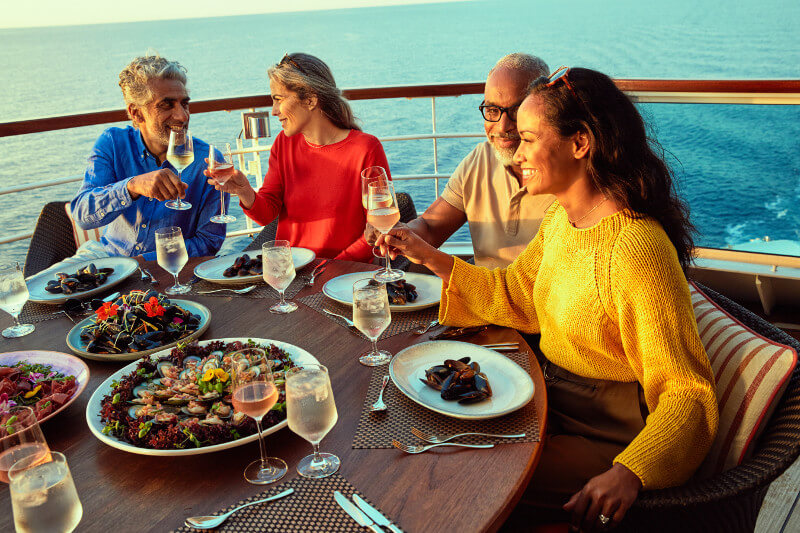 A happy group of Seabourn passengers enjoy dinner on the deck as the sun sets.