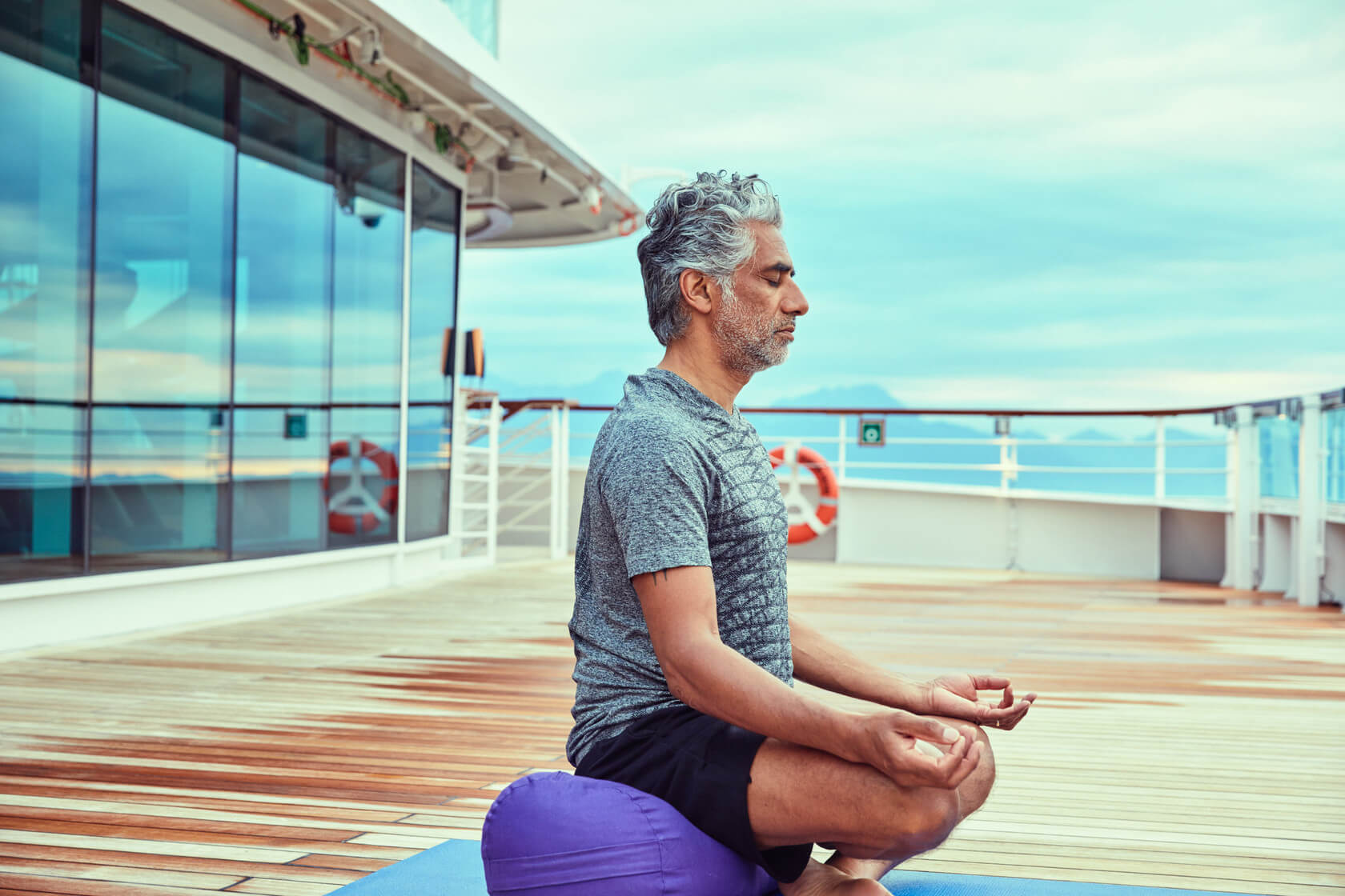 Under blue skies, a man practices meditation on the Seabourn Cruise Ship.