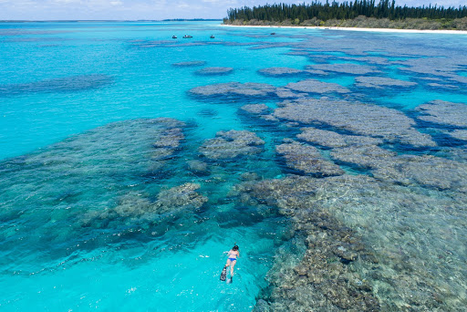 Seabourn passenger snorkles freely amongst coral in crystal clear turquoise water.